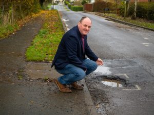 Shropshire Deserver Better than our roads falling apart. David Walker examining a persistent pothole in Park Hall